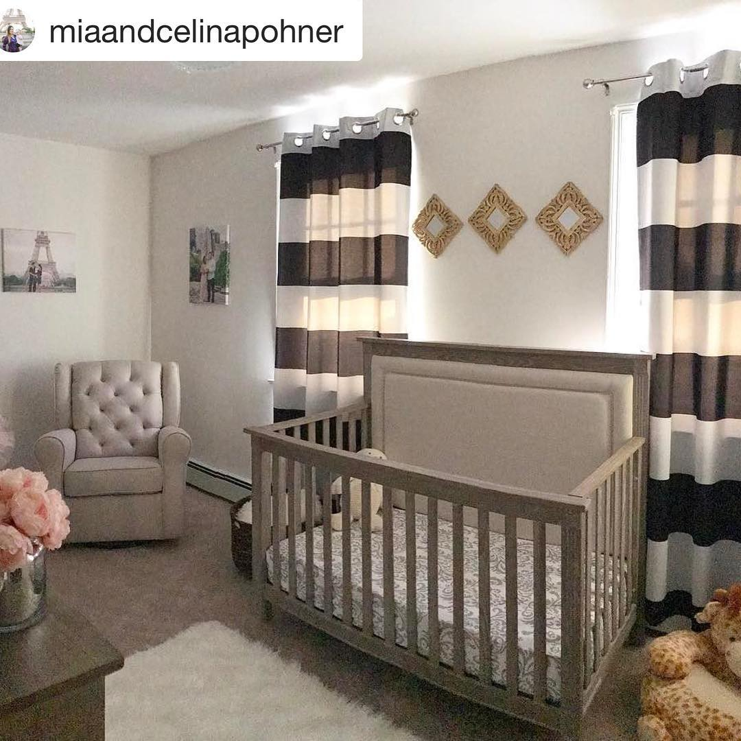 Baby nursery with black and white striped curtains, wooden crib with beige upholstered headboard panel