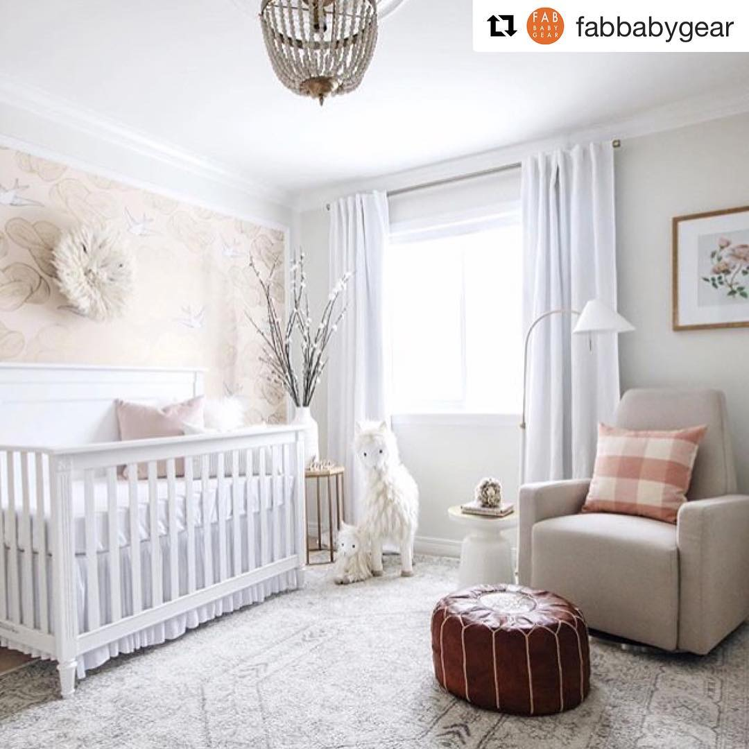 White nursery featuring a white crib and glider chair in linen beige and a brown ottoman