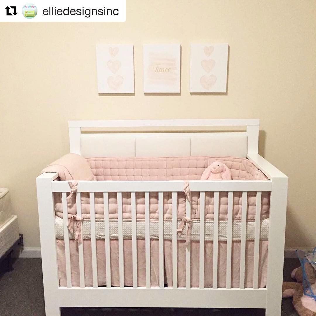 Yellow baby nursery with white sleek wooden crib with pink sheets