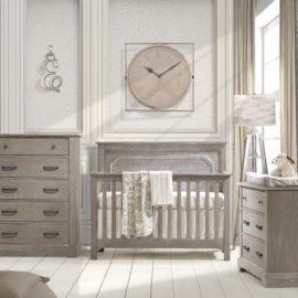 Baby nursery with white brick wall, big beige clock and sugarcane wooden 3 drawer dresser, 5 drawer dresser and crib