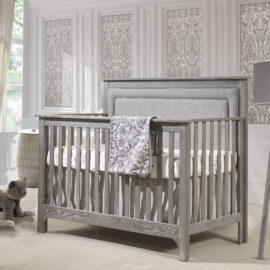 Baby nursery with grey and white wallpaper, with a grey wooden crib with a grey upholstered panel