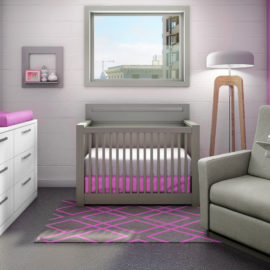 Baby nursery with white wall with a pink accent wall, grey sleek milano crib, a grey glider chiar and a white wooden double dresser