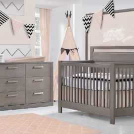 Pink baby room with pink rug, a pink teepee and grigio wooden convertible crib and double dresser, featuring a soft pink matty changing table