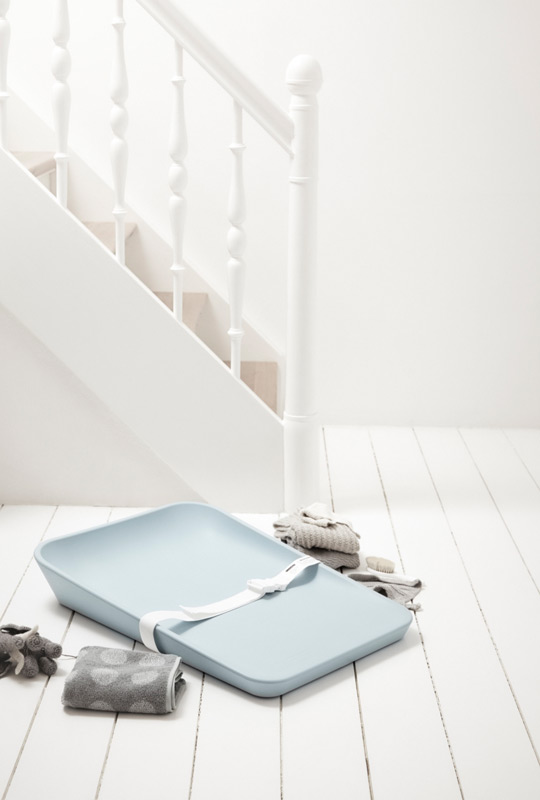 Matty changing tray in soft blue with white strap on a white wooden floor surrounded by grey folded towels