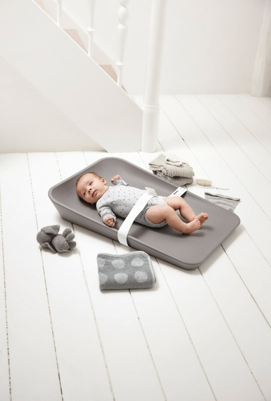 Baby strapped in with a white strap laying on a matty changing tray in grey surrounded by grey towels