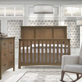 Grey and white baby room with elephant wallpaper, autumn wooden crib and double dresser and a rocking chair with white linen rocking chair