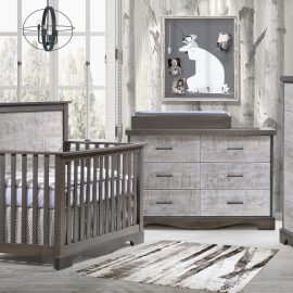 Baby nursery with white bark tree wallpaper, featuring dark wooden crib, 5 drawer dresser and double dresser with white bark facades