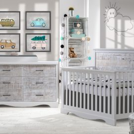 White baby nursery with framed photos of cars, with white wooden crib, double dresser with white bark facades and black metallic handles and white changing tray