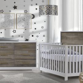 White bedroom with moon and star decals on walls, a white crib and double dresser with dark brown bark facades featuring a grey matty changing tray