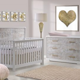 Pink baby nursery with framed golden heart and vibe letters, featuring a white crib and double dresser with white bark facade with antique brass pulls, a matty changing tray in light pink