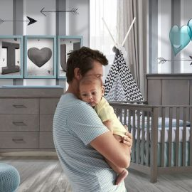 baby room with grey and white striped walls with blue hearts and framed letters with wooden floors, dark wood double dresser and crib with blue sheets, a blue ottoman with a dad holding baby