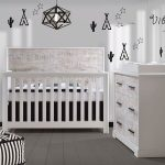 White bedroom with teepee and cactus decals on walls, a white crib and double dresser with white bark facades