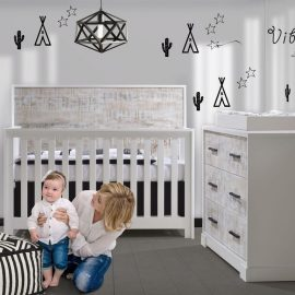 White bedroom with teepee and cactus decals on walls, a white crib and double dresser with white bark facades with a mom holding up baby