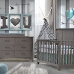 baby room with grey and white striped walls with blue hearts and framed letters with wooden floors, dark wood double dresser and crib with blue sheets, a blue ottoman