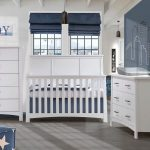white and blue baby nursery with framed JOY on wall and outline of city on the wall. With white double dresser, 5 drawer dresser and crib with grey matty changer