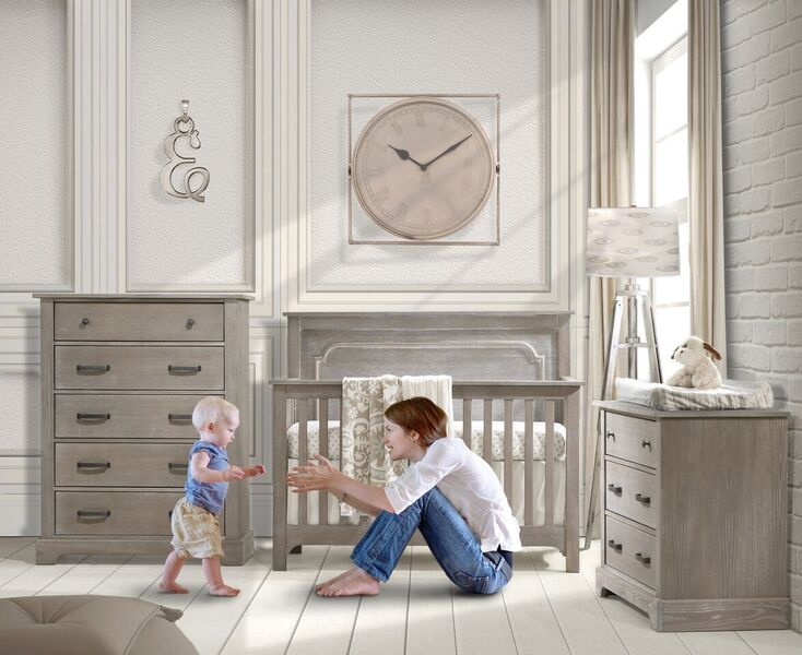 Baby nursery with white brick wall, big beige clock and sugarcane wooden 3 drawer dresser, 5 drawer dresser and crib with a mom reaching out to walking baby