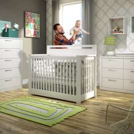 dad playing with baby in the nursery with white furniture