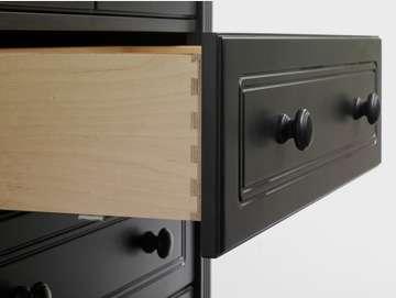close up of open drawer of a black dresser