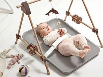 baby laying on a grey changing mat with a safety belt attached, playing with a beige mobile