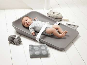 baby laying on a grey changing mat with safety belt attachedplaced on the floor