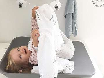 Toddler girl laying on a grey changing mat with her legs in the air