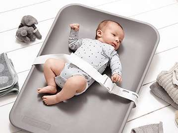 baby laying on a grey changing mat with a safety belt around him